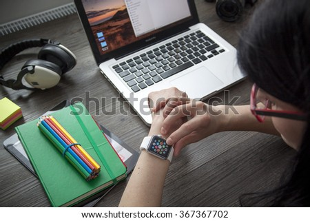 Prague, Czech Republic - January 23, 2016: Photo of women taping on Apple Watch at Home workplace with Apple Macbook Pro, iPad produced by Apple Computer, Inc..