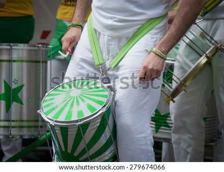 PRAGUE, CZECH REPUBLIC - MAY 3, 2015: A band drummer  wellcoming the succesful participants of Prague Marathon at finish of the race - closeup of his green white drum and drumsticks in action - stock photo