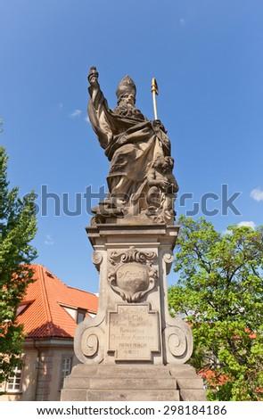 PRAGUE, CZECH REPUBLIC - MAY 10, 2015: Statue of St. Augustine (circa 1708) on the balustrade of famous Charles Bridge in Prague (UNESCO site). Sculptor Jan Bedrich Kohl - stock photo