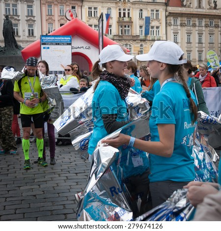 PRAGUE, CZECH REPUBLIC - MAY 3, 2015:  Young female marathon organizers giving runners who have just finished the Volkswagen Prague Marathon aluminum foils to keep them warm at Old Tow Square, Prague - stock photo