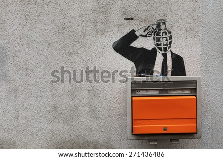PRAGUE, CZECH REPUBLIC - NOVEMBER 11, 2012: Grenade-headed person blowing his head up depicted in the street graffiti next to the letter box in Prague, Czech Republic. - stock photo