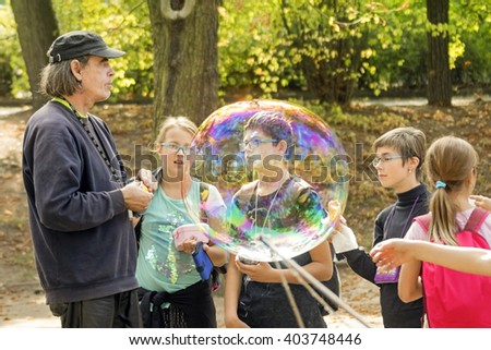 PRAGUE, CZECH REPUBLIC, 15 OCTOBER, 2015: Children wearing glasses and a grown man inflate huge soap bubbles in summer park