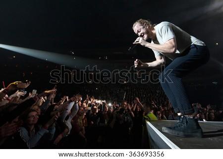 PRAGUE - JANUARY 16: Singer Dan Reynolds of American rock band Imagine Dragons during performance in Prague, Czech republic, January 16, 2016. - stock photo