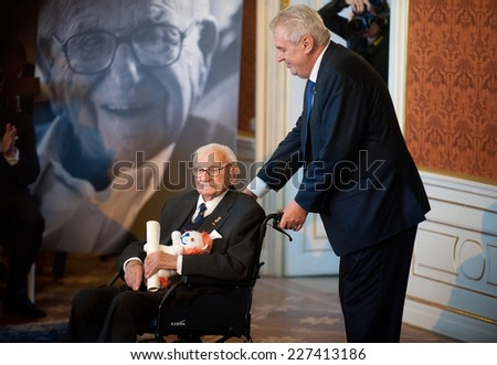 PRAGUE - OCTOBER 28: Czech President Milos Zeman (R) pushes Sir Nicholas Winton (L) in his wheelchair after he was awarded the Order of the White Lion, in Prague, Czech Republic, 28 October 2014. - stock photo