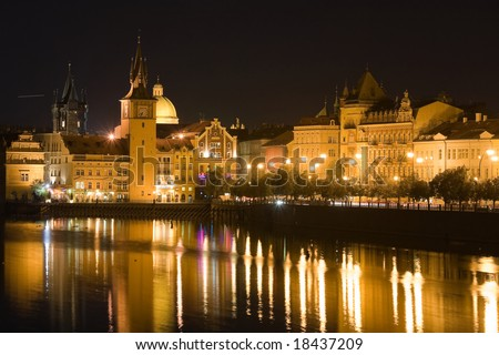 Prague Old town riverbank in night with reflection in Vltava river.