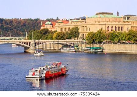 Prague scenery, passenger boats on Vltava river and Neo-Renaissance architecture of the Rudolfinum Concert Hall in Prague, Czech Republic - stock photo