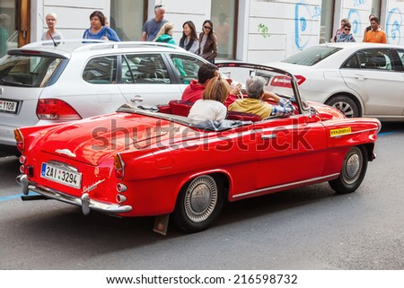 PRAGUE - SEPTEMBER 04: classical red Skoda for sightseeing with unidentified people on September 04, 2014 in Prague. City is home to many cultural attracts in historic centre, UNESCO listed - stock photo