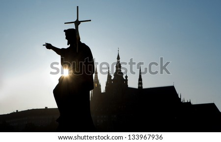Prague - silhouette of Saint John the Baptist statue from Charles bridge and cathedral - stock photo