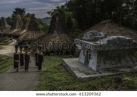 Praing traditional village, West Sumba, NTT, Indonesia - March 24, 2017 : Women carrying ceramic water pots on their head in Praing traditional village