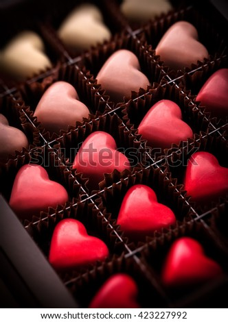 Pralines heart shaped closeup gradually colored in luxury brown box package - stock photo