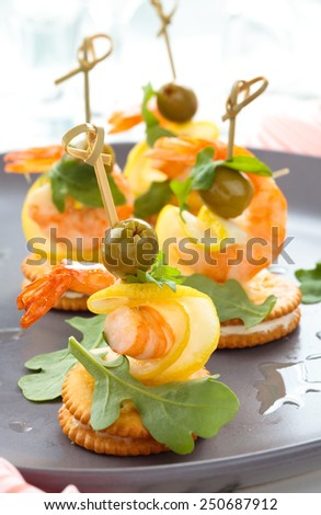 Prawn canapes with arugula leaves and olives. - stock photo