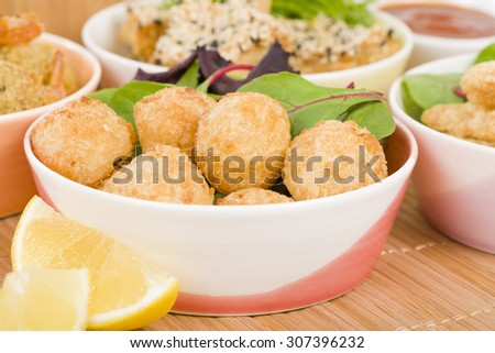 Prawn & Coconut Popcorn - Shrimp meat coated in coconut batter, breaded and deep fried. Other party food on background. - stock photo