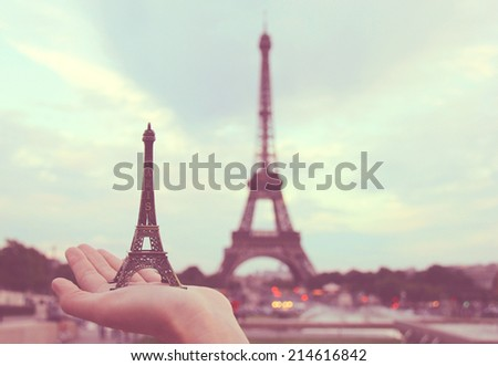 Pray for Paris, hand holding eiffel tower model in paris, retro filter effect - stock photo