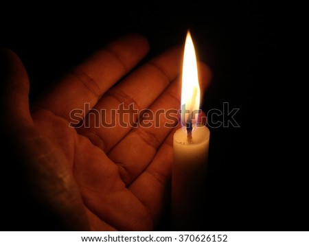 prayer candle in hand