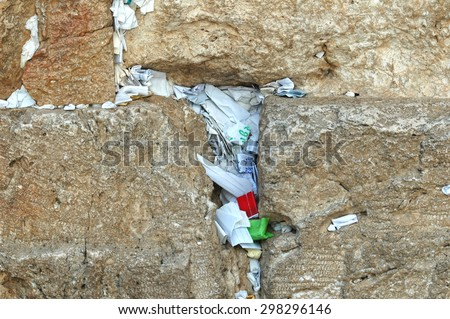 Prayer notes - zooming in on the slips of paper containing prayers in the cracks of the holy Western Wall, Jerusalem, Israel - stock photo