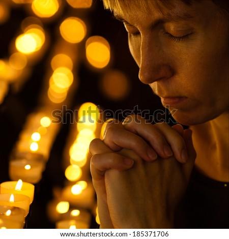 Prayer praying in Catholic church near candles. Religion concept. - stock photo