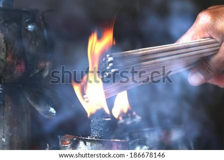 Prayers burning incense sticks on a temple fire - stock photo