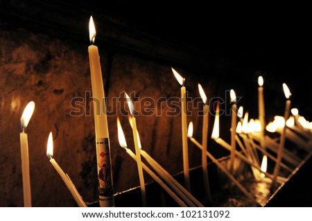Prayers candles in the Church of the Holy Sepulchre in Jerusalem old city, Israel. - stock photo