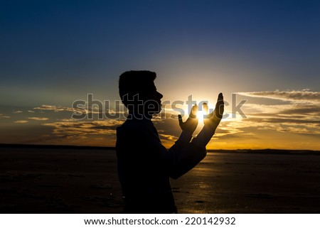 Praying at sunset - stock photo