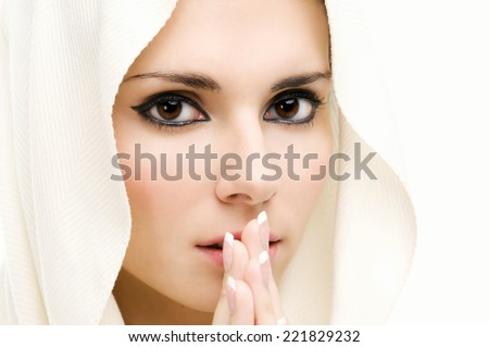 Praying beautiful woman with covered head. Close-up. Isolated image - stock photo