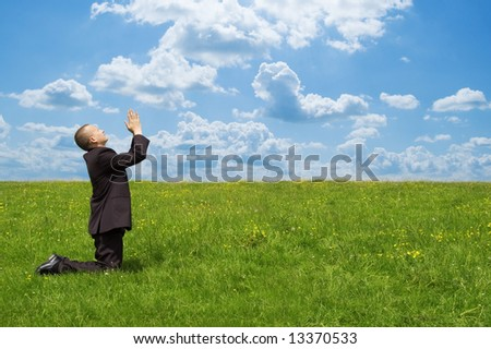 praying businessman on grsaa fiield