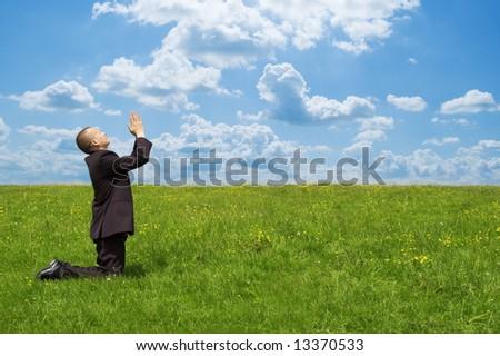 praying businessman on grsaa fiield - stock photo