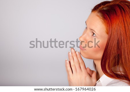 Praying girl staring back at the sky with space for text.