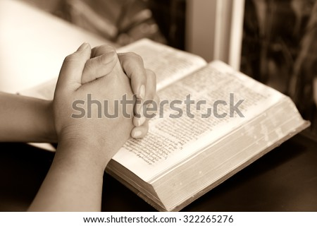 praying hand and book on desk showing religion concept-Woman hands praying with a bible,Reading bible and pray - stock photo
