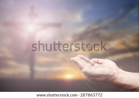 Praying Hand and the cross blurred background. - stock photo