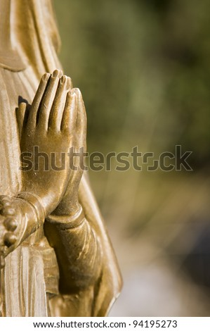praying hands clasped pf a statue