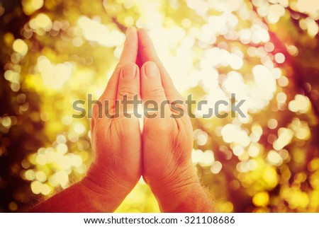 Praying hands, cross shaped lens flare. - stock photo