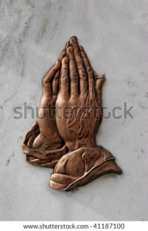praying hands embossed on a marble plaque - stock photo