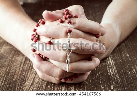 Praying hands holding red rosary with  cross  - stock photo