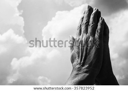 praying hands in harsh light with cloudy sky in black and white - stock photo
