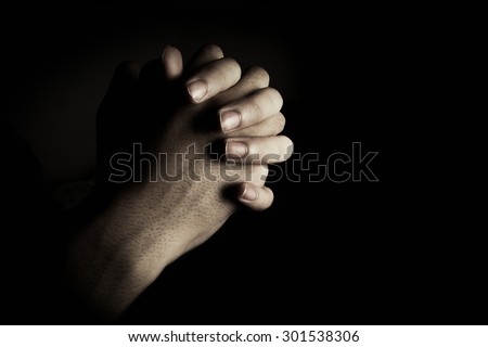Praying hands is in the dark with light on the hands. - stock photo