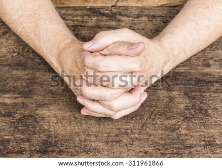 praying hands of the man on wooden background - stock photo