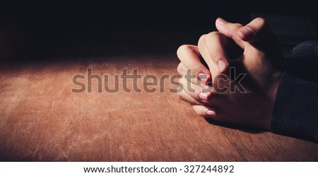 Praying hands of young man on a wooden desk background. - stock photo