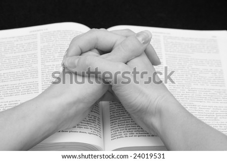 Praying hands on an open bible - stock photo