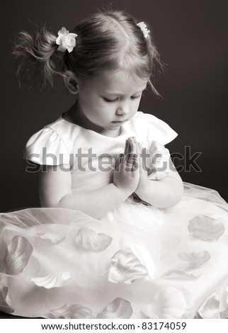 Praying little girl on gray background