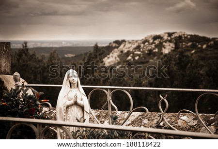 Praying Madonna statue with a rosary behind  the metal grave fence at the cemetery in Les Baux-de-Provence (Provence, France) and a beautiful landscape at backgrounds. Aged photo. Sepia. - stock photo