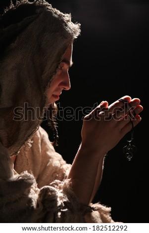 praying man in monk's clothing - stock photo