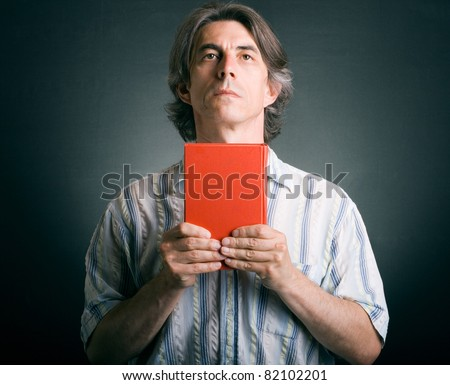 Praying man with Bible in hand. - stock photo