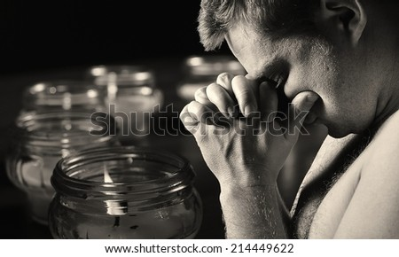 Praying man with candles on background. MANY OTHER PHOTOS FROM THIS SERIES IN MY PORTFOLIO.  - stock photo