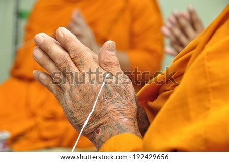 praying monk hand with tattoo on hand - stock photo
