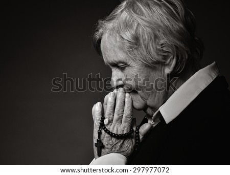 Praying senior woman. MANY OTHER PHOTOS FROM THIS SERIES IN MY PORTFOLIO. - stock photo