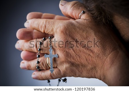 Praying with a rosary - stock photo