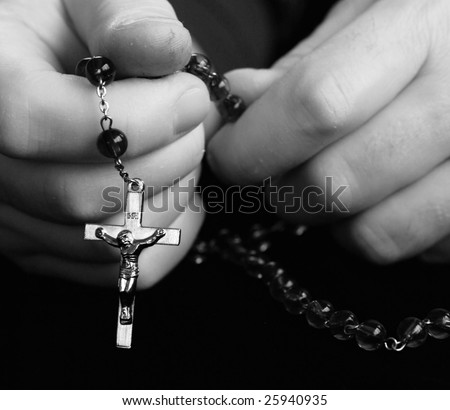 praying with rosary beads - stock photo