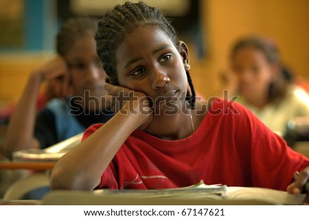 Pre-adolescent boy daydreaming at desk - stock photo
