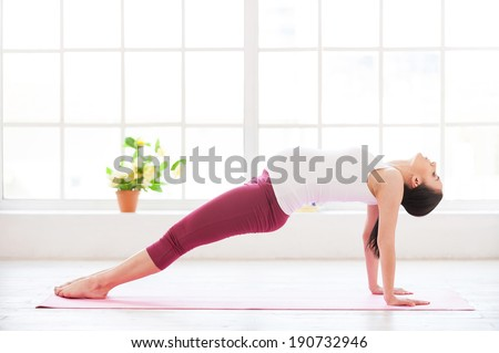 Pre-natal exercise. Beautiful pregnant woman exercising at home  - stock photo