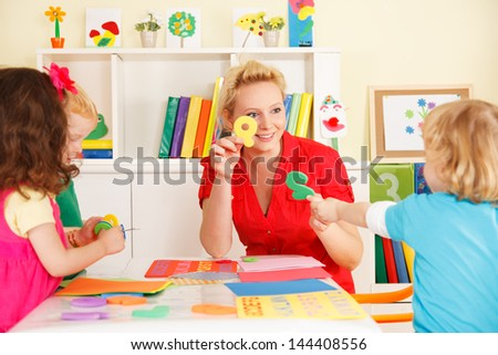 pre-school children in the classroom with the teacher - stock photo